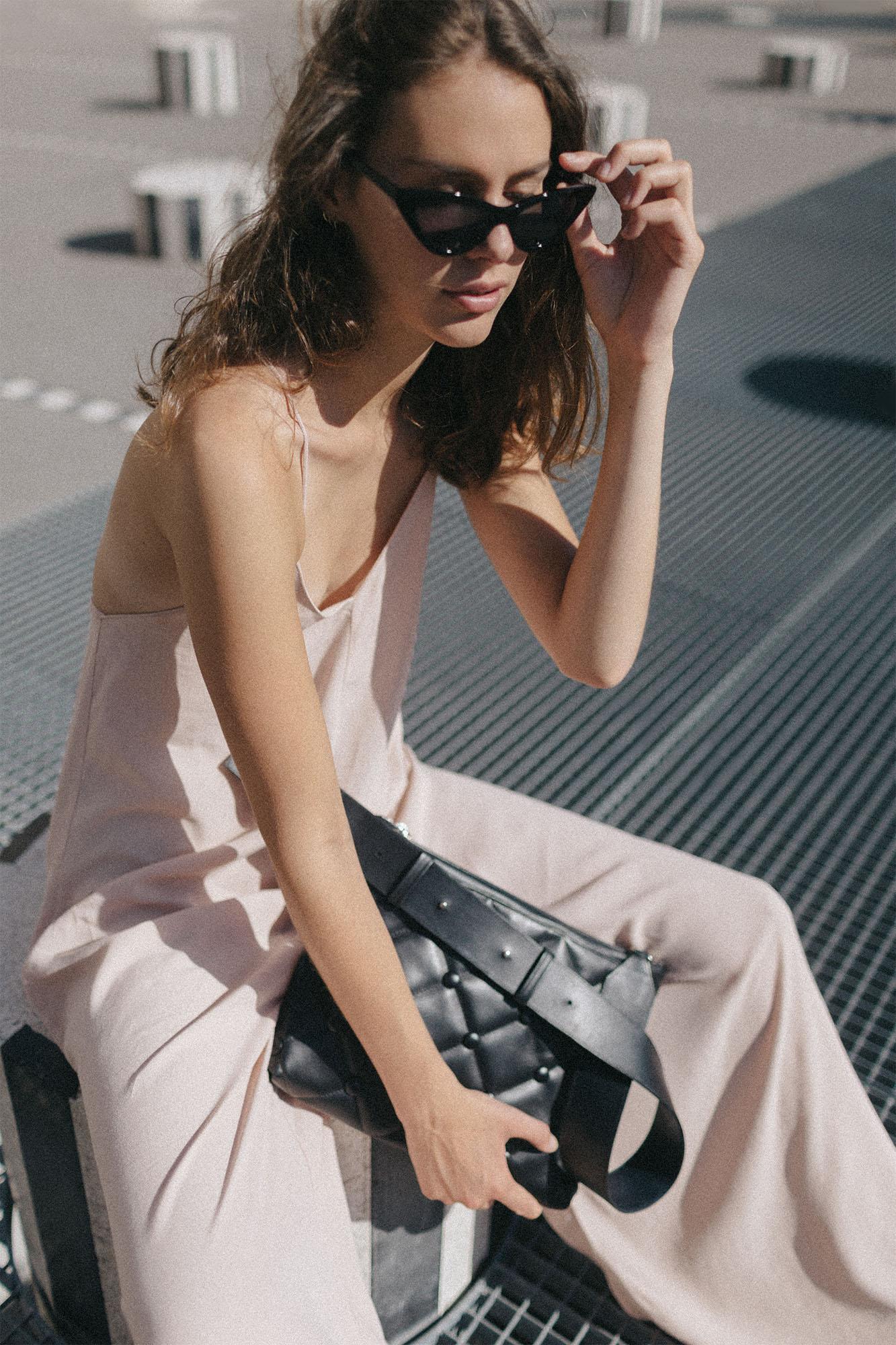 Model sitting on the Colonnes de Buren in Palais Royal with Laimushka black leather handbag