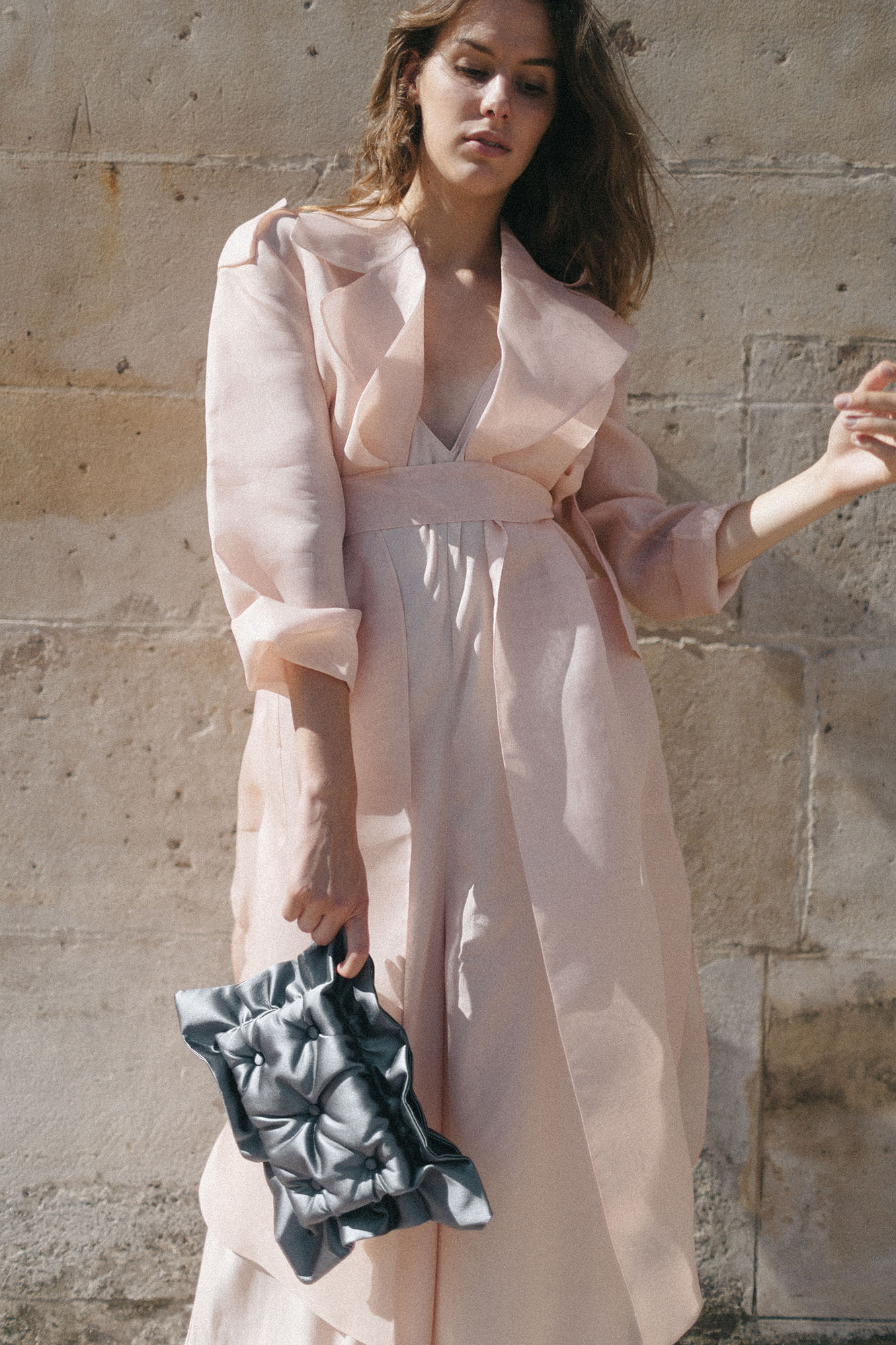 Model in front of the wall in Palais Royal with Laimushka dark grey quilted silk pillow clutch bag