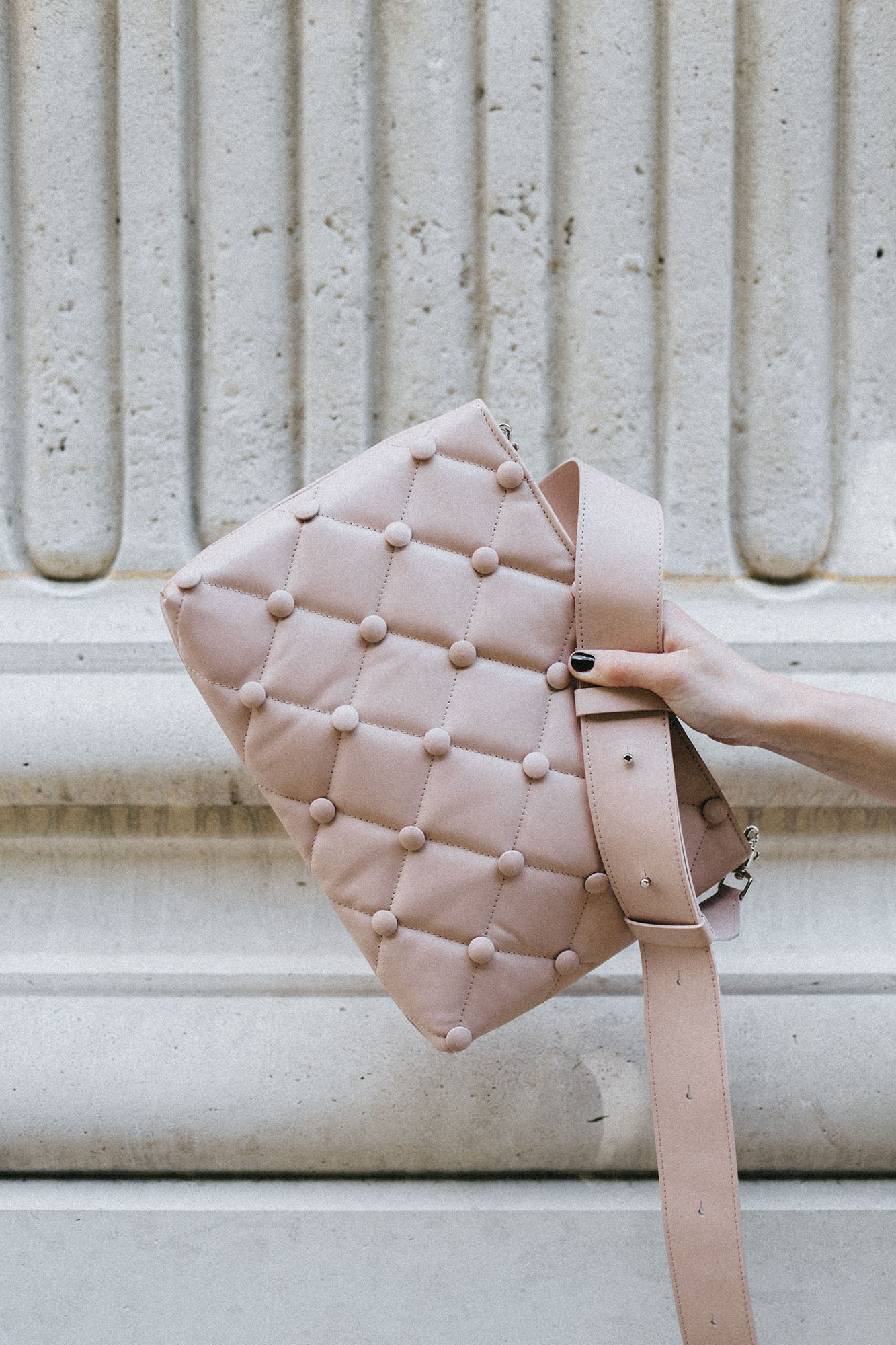 Laimushka nude leather quilted handbag with shoulder strap in front of the wall in Palais Royal