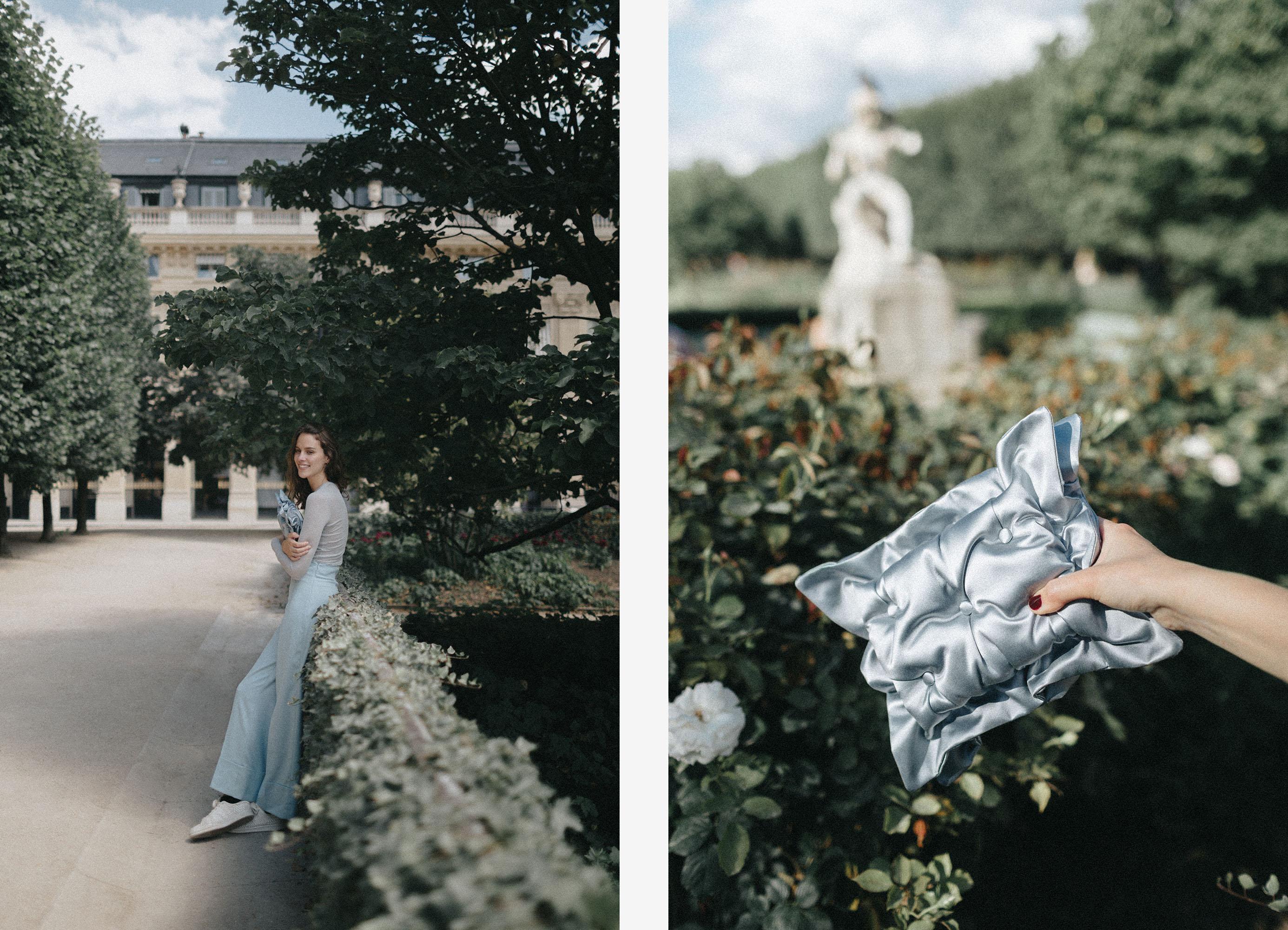 Model in Frech garden with Laimushka light blue silk clutch bag in Paris. Laimushka light blue silk pillow bag in French garden in Paris