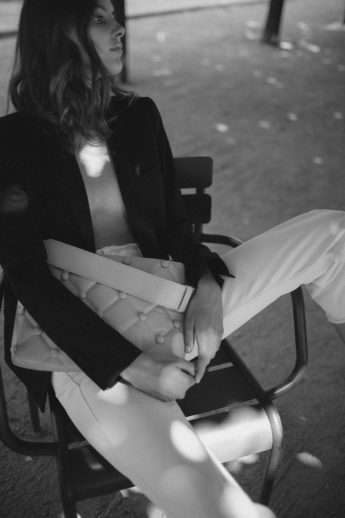 Black and white photo of a model with Laimushka quilted leather handbag sitting on a chair in Palais Royal in Paris