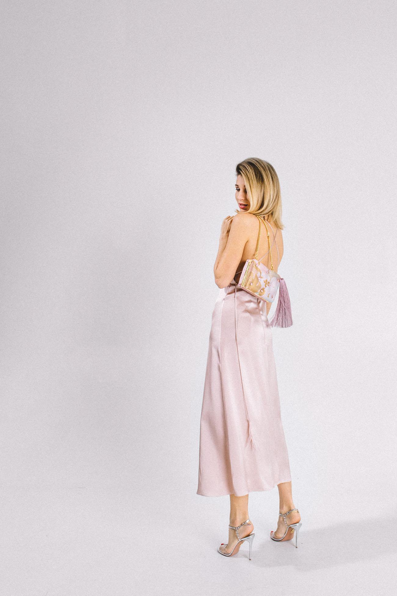 Katya Silchenko in a bias cut silk slip dress with Laimushka silk clutch bag with tassel