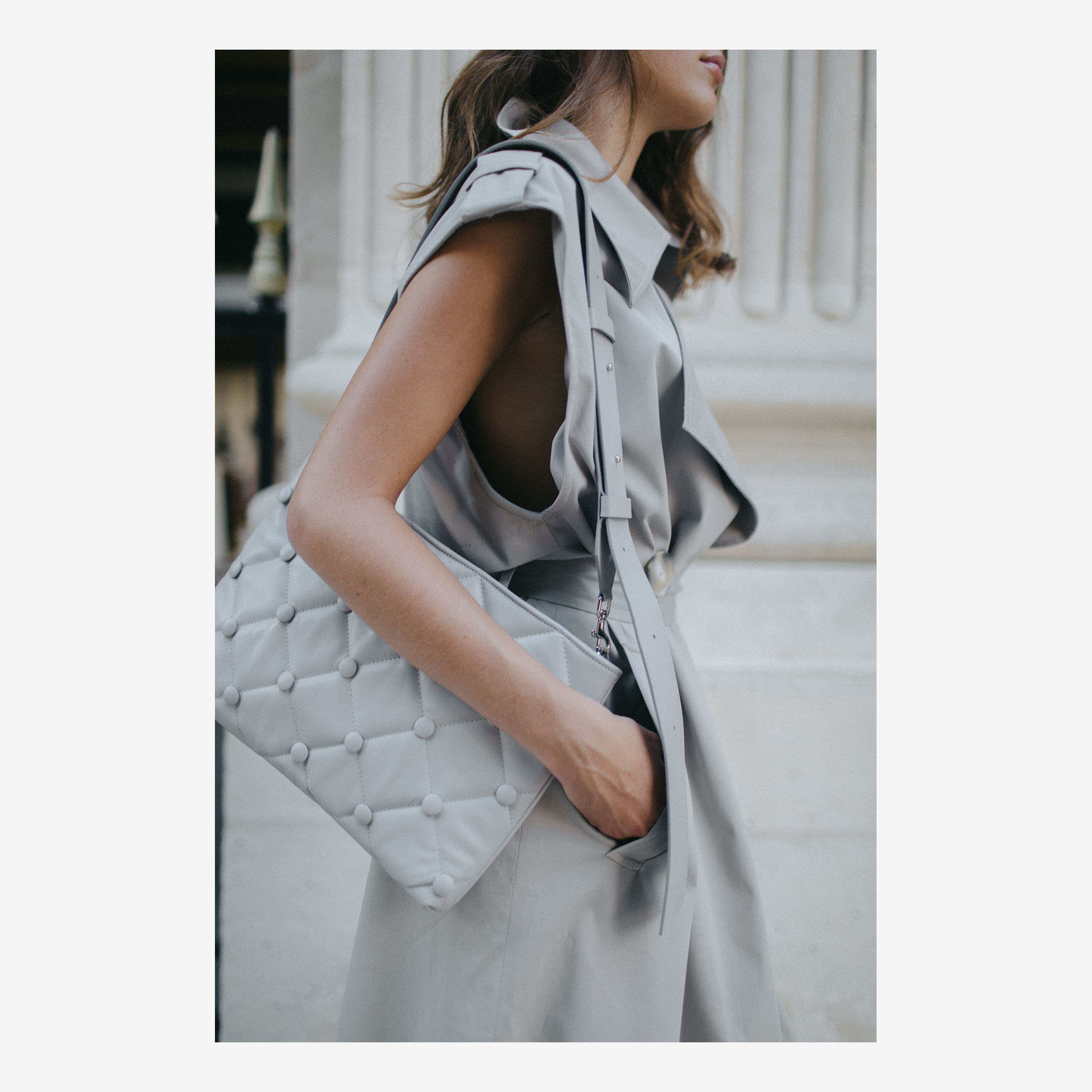 Model in trench coat with Laimushka grey leather shoulder bag in Paris, Palais Royal
