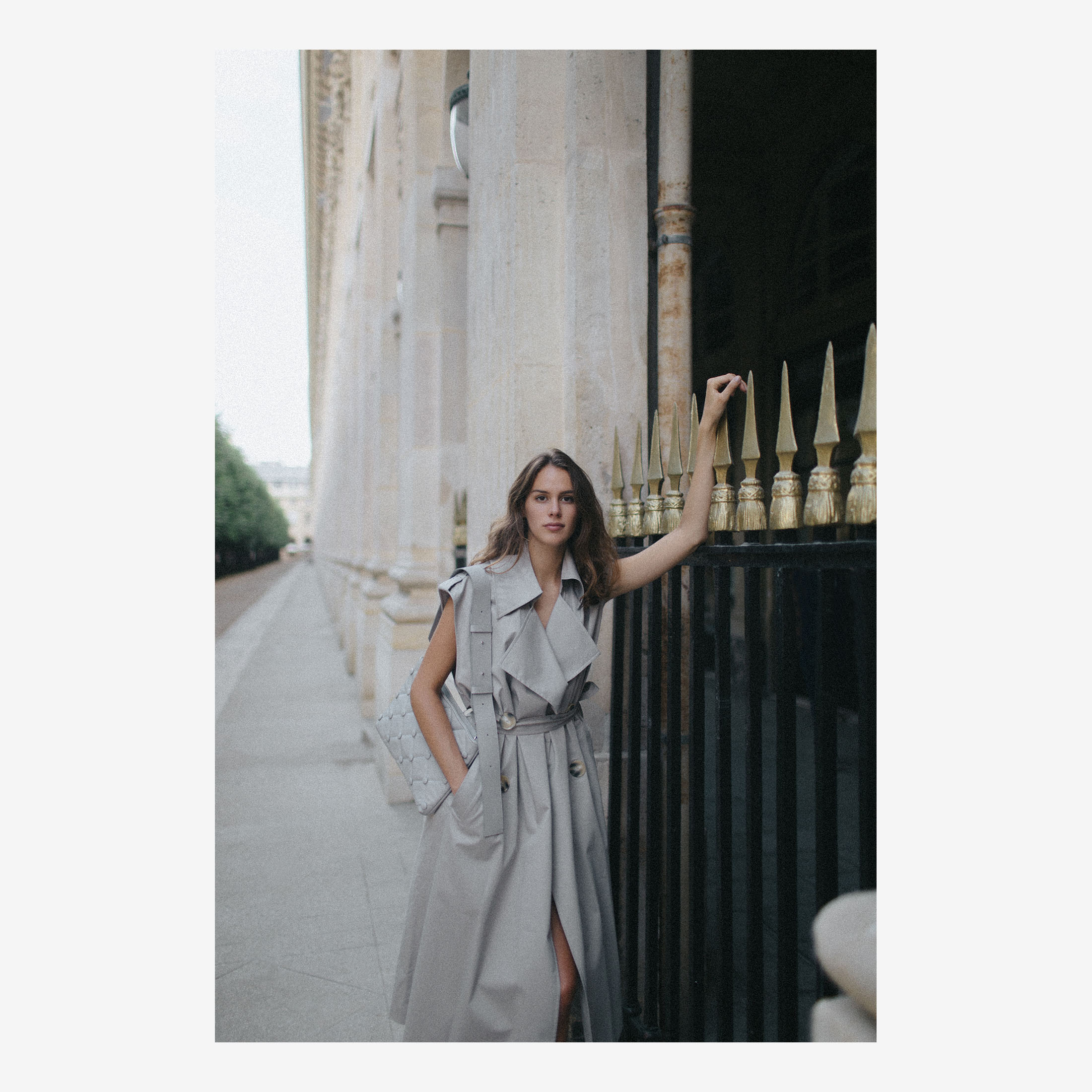 Woman in a trench coat with grey leather shoulder bag in Paris, Palais Royal