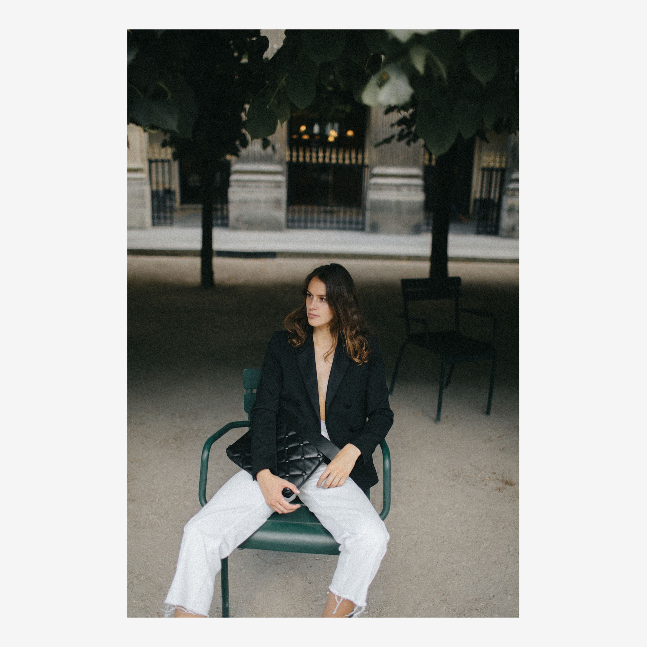 Woman sitting on a chair in Palais Royal with Laimushka black leather handbag