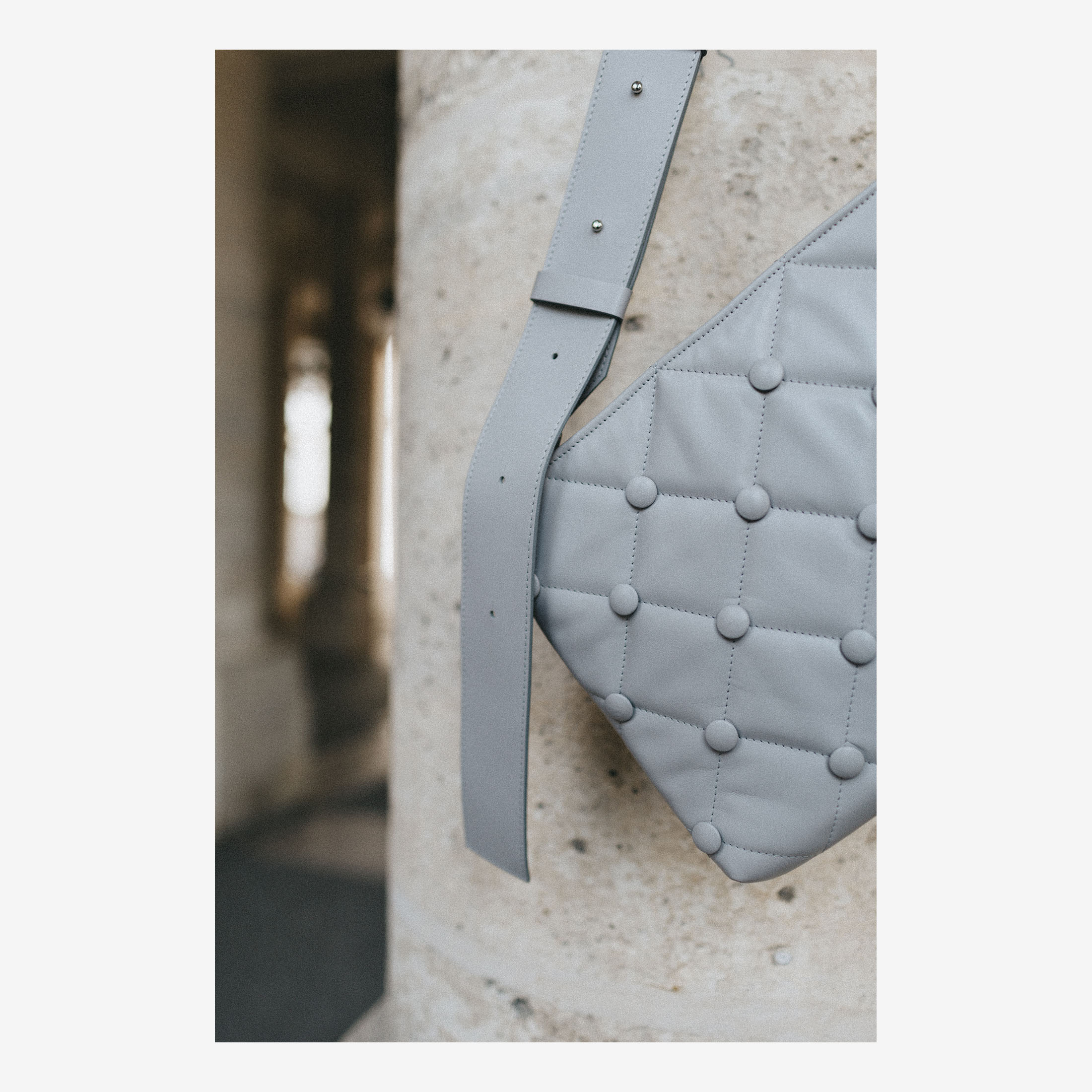 Laimushka grey leather quilted handbag with shoulder strap in front of the column in Palais Royale