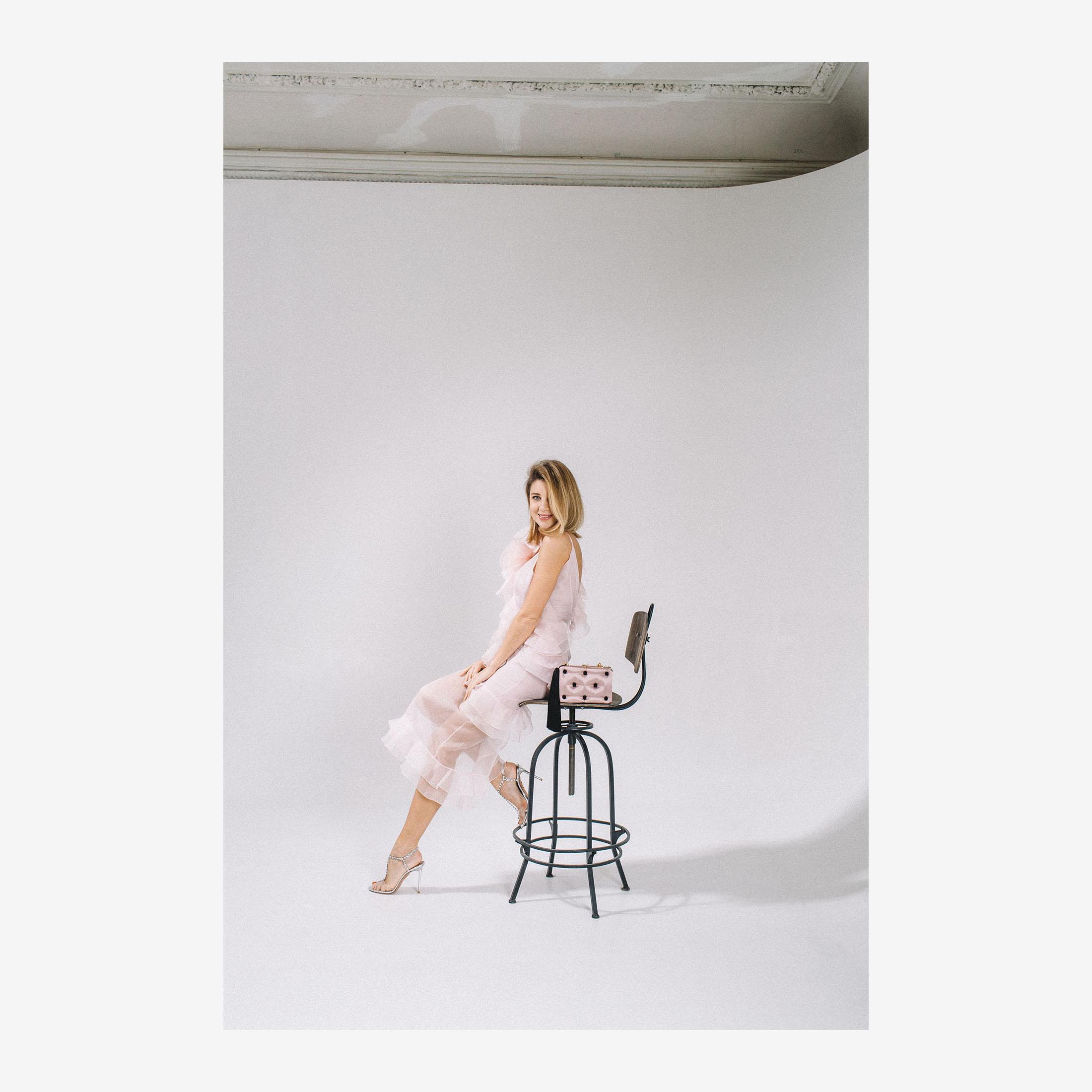 Katya Silchenko with Laimsuhka pastel pink silk clutch bag with tassel